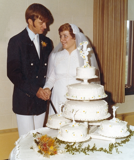 Tom and I cutting the cake with diasies